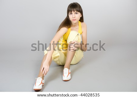 The young beautiful girl in a yellow vest and sports footwear on a grey background