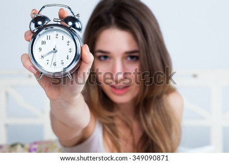 The young beautiful girl in bed. The clock service is in the foreground