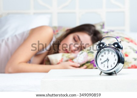 The young beautiful girl sleeping in bed. The clock service is in the foreground - stock photo