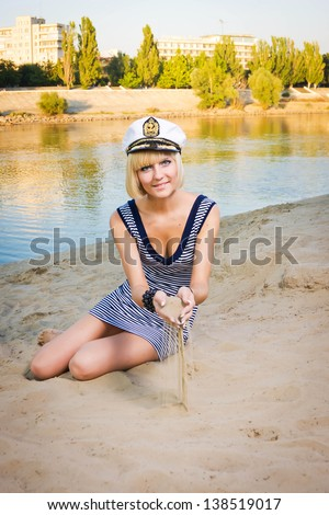 The young beautiful girl strews sand from hand on a beach
