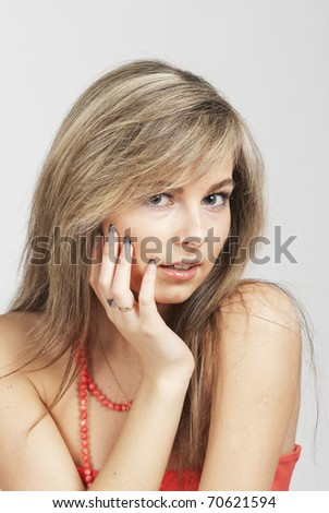 The young beautiful girl the blond with a long straight hair in a red dress smiles in the chamber