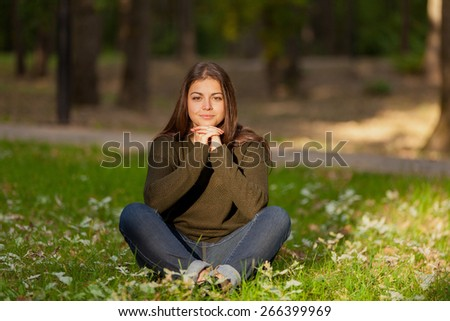 The young beautiful girl with long hair, meditates in autumn park - stock photo