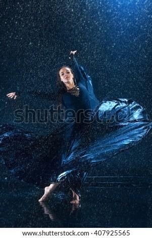 The young beautiful modern dancer dancing under water drops - stock photo