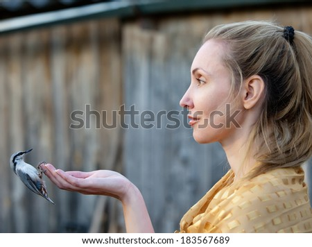 The young beautiful woman feeds a bird from a hand