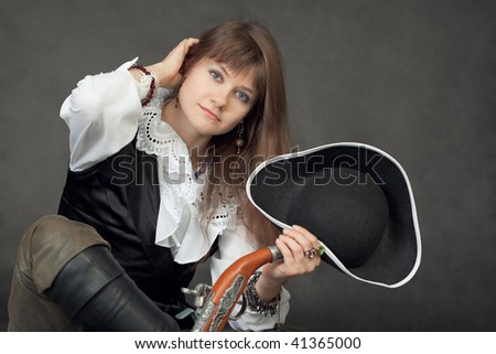 The young beautiful woman in a costume of the pirate on a black background