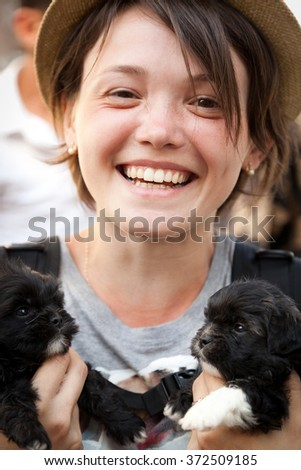 the young beautiful woman in a hat holds two little puppies in hand - stock photo