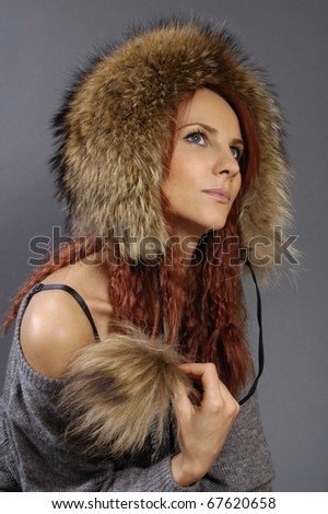 The young beautiful woman in a winter cap from fur of a raccoon on a gray background