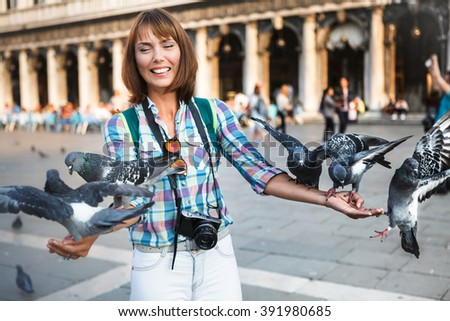 The young beauty girl tourist laughing feeding the pigeons in Piazza San Marco. Famous sight and attraction in Italy in Venice - stock photo