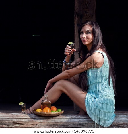 The young beauty with tequila in old wooden house - stock photo