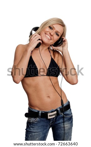 The young blonde girl listens to music in black ear-phones - stock photo