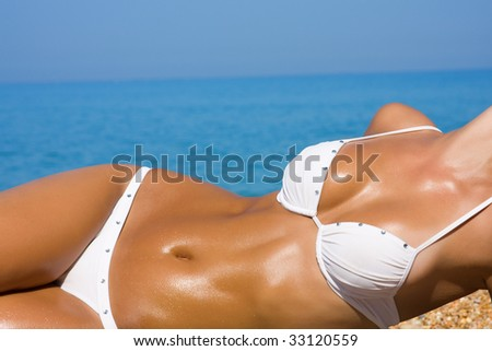 The young blonde girl with a beautiful body sunbathes on a beach in a white bathing suit against the sea - stock photo