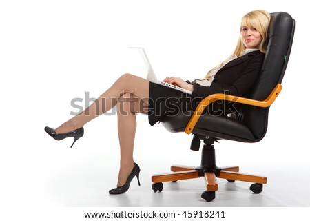 The young blonde the business woman sits in armchair and holds a computer