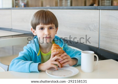 The young boy is eating lunch in the school cafeteria