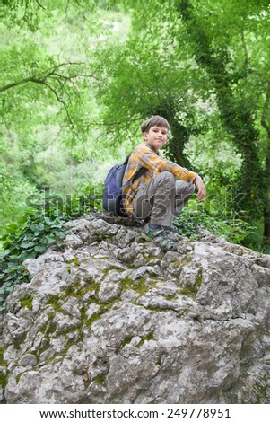 The young boy sits on big stone in green summer forest - stock photo