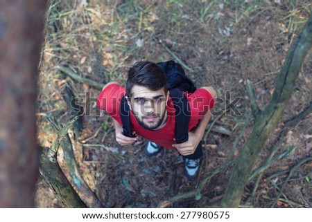 The young boy with a backpack stand under a tree - stock photo