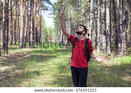 The young boy with a phone stand in forest - stock photo