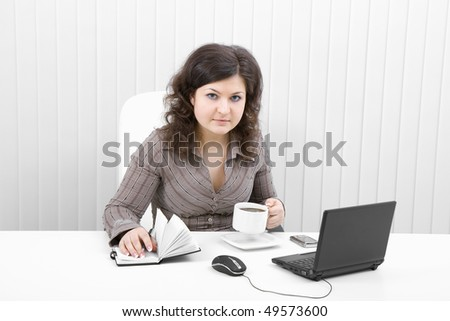 The young brunette at office with the laptop and coffee