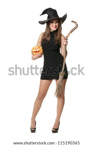 The  young brunette witch with a broom and pumpkin - stock photo