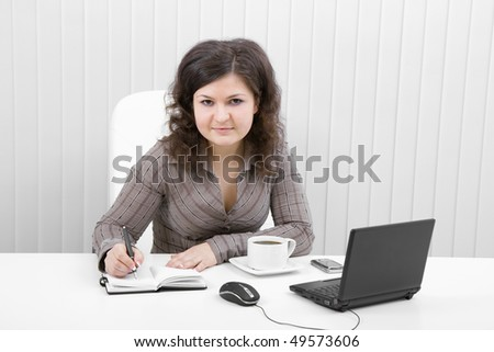 The young brunette works at office writing down in notebook