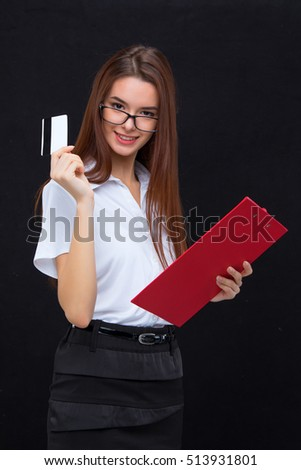The young business woman in glasses with credit card and tablet for notes on a gray background