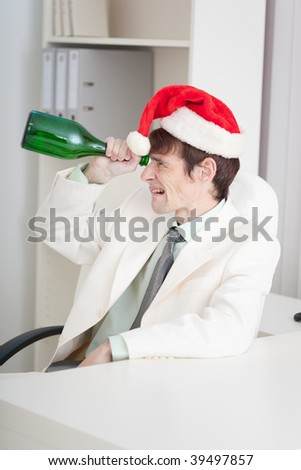 The young businessman celebrates Christmases at office on a workplace