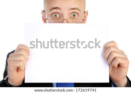 The young businessman holds a white sheet of paper