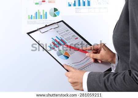 The young businesswoman showing graphs by pen - stock photo
