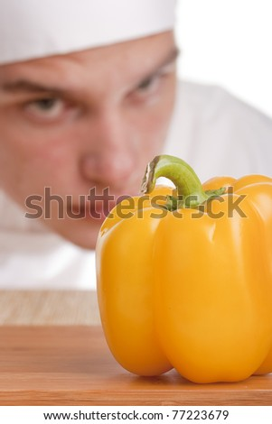 The young chef in chef's hat is considering a pepper. - stock photo