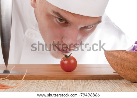 The young chef in chef's hat is considering a tomato. - stock photo