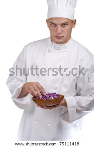 The young chef in uniform and chef's hat in his hands chopped red cabbage. - stock photo