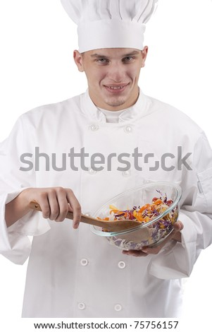 The young chef in uniform and chef's hat in the bowl of salad mixes. - stock photo