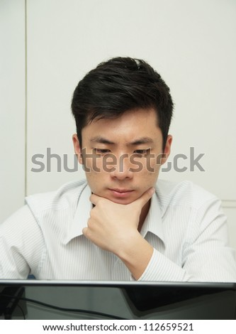 The young chinese businessman concentrate this job - stock photo