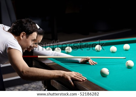 The young couple aim before blow in billiards