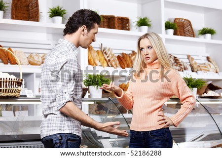The young couple argues in grocery shop - stock photo
