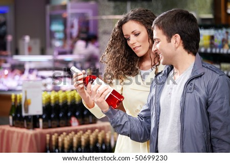 The young couple chooses a wine bottle in shop - stock photo