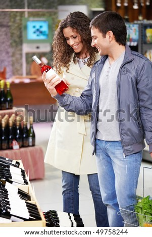 The young couple chooses wine in shop - stock photo