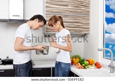 The young couple considers pan contents at kitchen