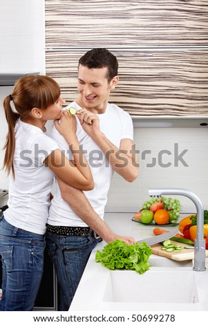 The young couple cuts vegetables at kitchen - stock photo