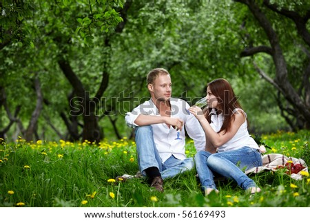 The young couple drinks champagne in park