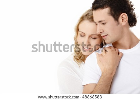 The young couple embraces on a white background - stock photo