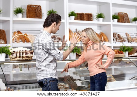 The young couple quarrels in a baker's shop - stock photo