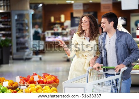 The young couple with the cart goes on shop - stock photo