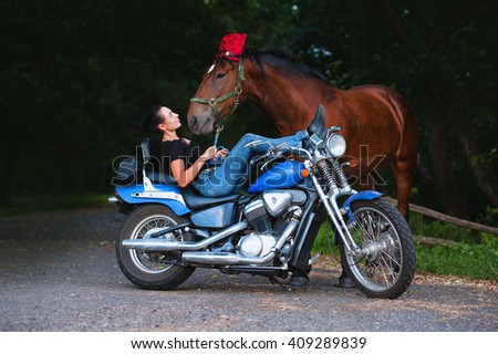 The young dark-haired woman lies on a blue motorcycle and holds a number of his horse. Horsewoman with the living and the iron horses.The horse at the head bandana and motorcycle goggles. - stock photo
