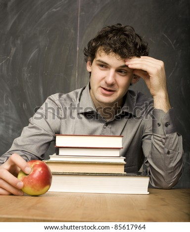 The young emotional student with the books and red apple in class room, at blackboard - stock photo