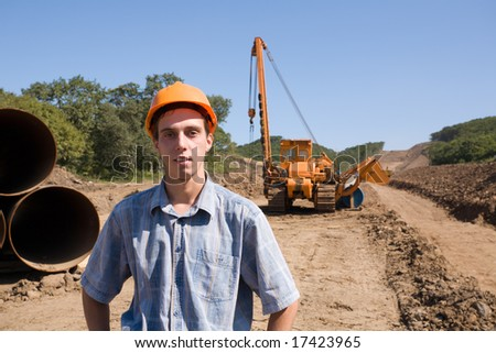The young engineer on a working platform on stacking a new oil pipeline. - stock photo