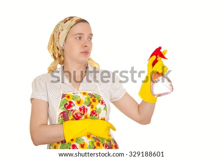 The young European woman in an apron and hand in yellow glove with red using spray application on a white background