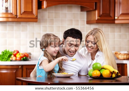 The young family has breakfast with the child on kitchen - stock photo