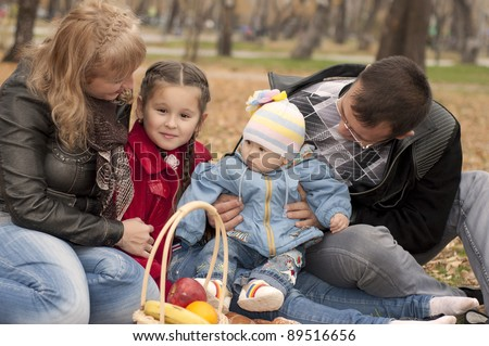 The young family in park, sits on a ground and happy