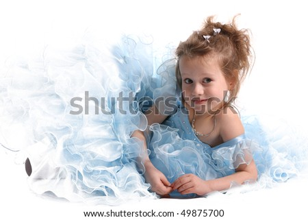 The young fine   girl (child) in a blue dress lays on a white background