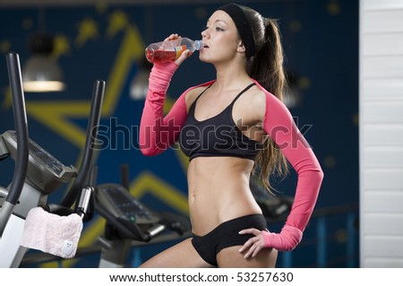 The young girl after training drinks water - stock photo
